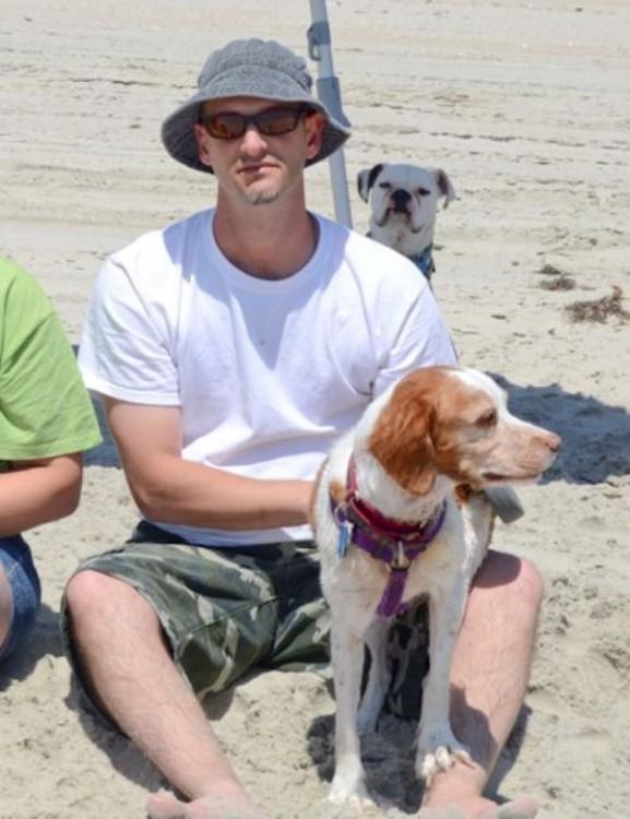 fotografía de un chico a lado de un perro con otro perro detrás de ellos