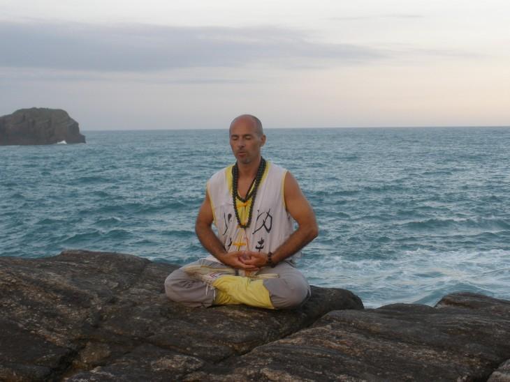hombre sentado sobre unas rocas frente al mar meditando