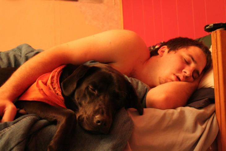 Chico dormido en una cama abrazado de su perro