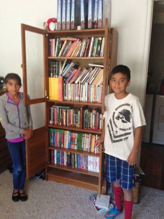 Mateo y su hermana Jazmín junto a un librero
