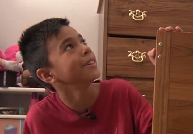 Mateo el niño que pidió libros a un cartero mirando su librero lleno de libros