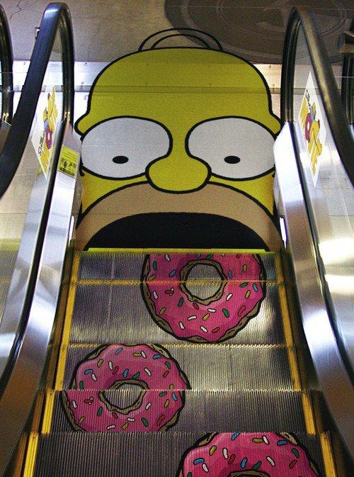 Escaleras eléctricas con forma de donas dirigiéndose hacia una cara de homero Simpson