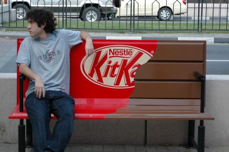 Banca en forma de chocolate KitKat Nestle y un chico sentado en ella