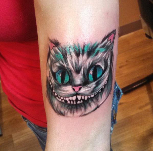 """Tatuaje del gato sonriente de """"Alicia en el país de las maravillas"""" en un brazo"""