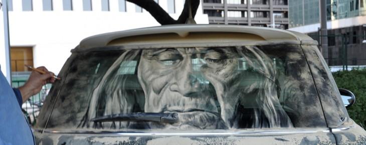 cara de un hombre echa con tierra en el parabrisas trasero de un coche
