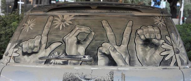 manos formando la palabra love en el parabrisas sucio de un coche