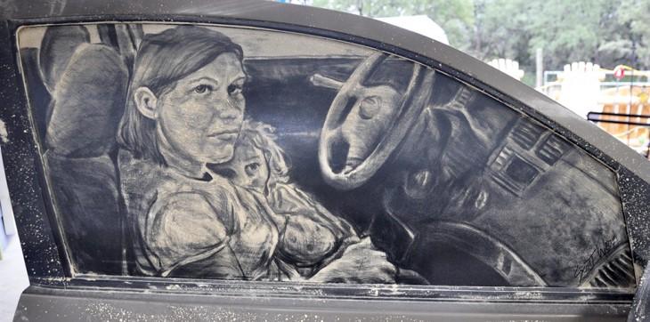 vidrio de una puerta de coche con el dibujo de una mujer con un bebé en sus brazos