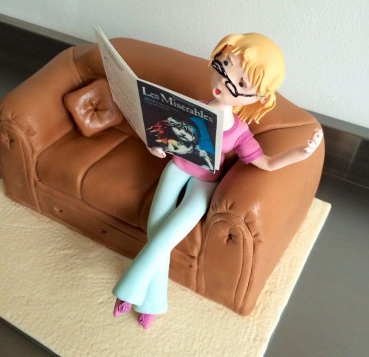 chica leyendo una revista sobre un pastel en forma de sofá