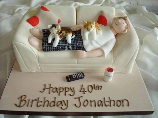 pastel de cumpleaños para un chico acostado en un sillón con dos gatos