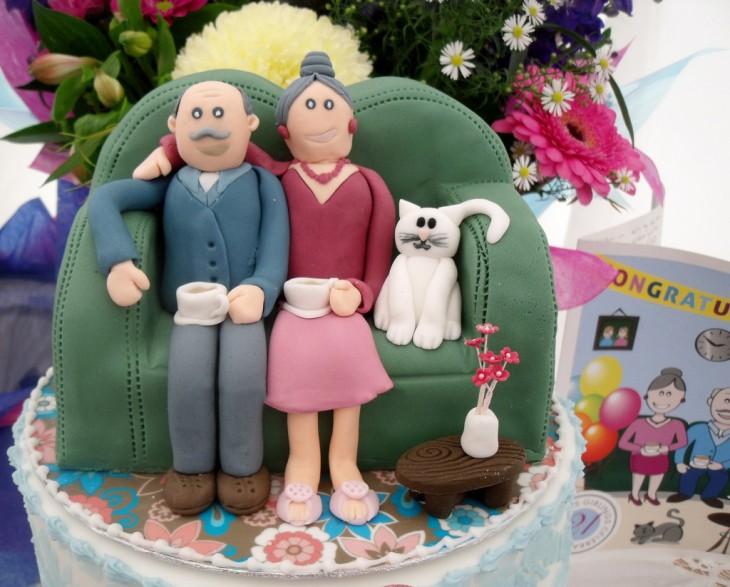 pastel de dos ancianos sentados sillón con un gato a lado de ellos