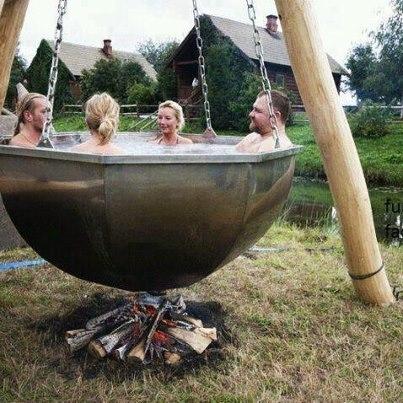 Personas dentro de una caldera llena de agua sobre una fogata