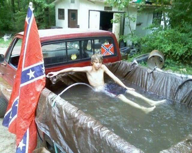 Chico sobre la caja de una camioneta con agua y una bandera