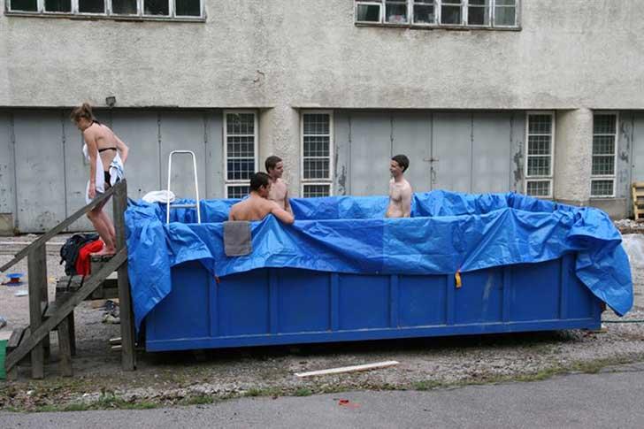 personas dentro de un gran bote de basura lleno de agua