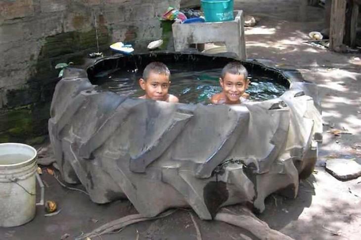 Niños dentro de una llanta enorme con agua dentro