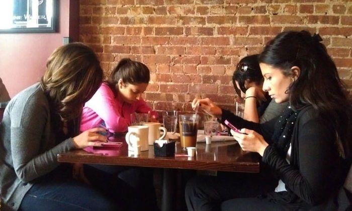 chicas sentadas en la mesa de un restaurante con el celular en las manos