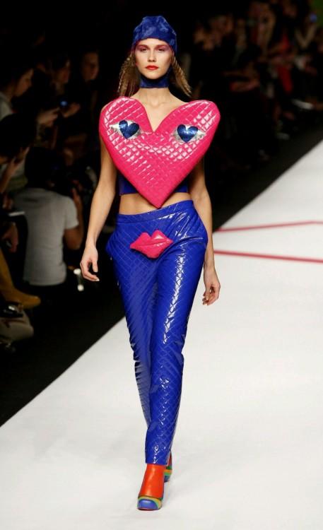 Modelo en una pasarela con un pantalón con una boca y en su parte de arriba con un corazón
