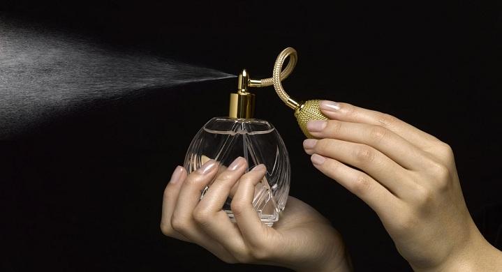 Manos sosteniendo un perfume y aplastandolo para que salga