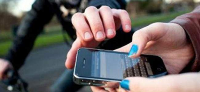 Manos con un celular y otra persona intentando quitarselo