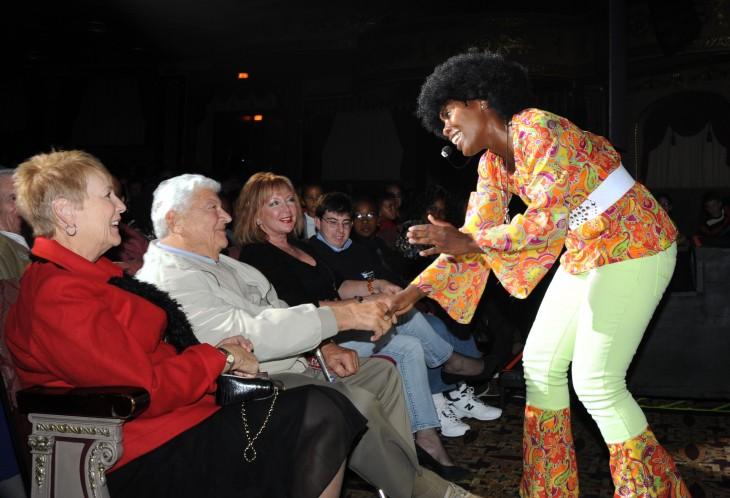 Mujer saludando a unas personas que están sentadas en las bancas de un auditorio