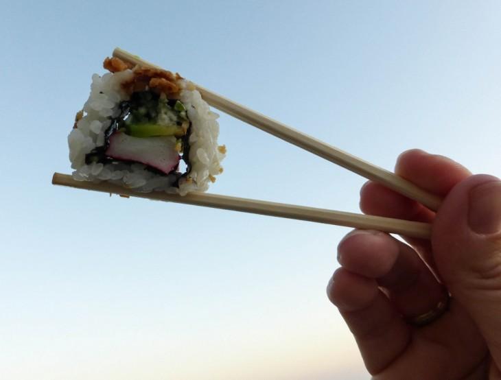 Manos de una persona sosteniendo sushi con palillos chinos
