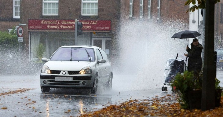 Carro pasando por un charco y mojando a una persona que va por la calle