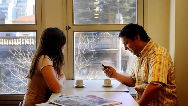 Una pareja sentada a la mesa cerca de una ventana con dos cafés sobre la mesa