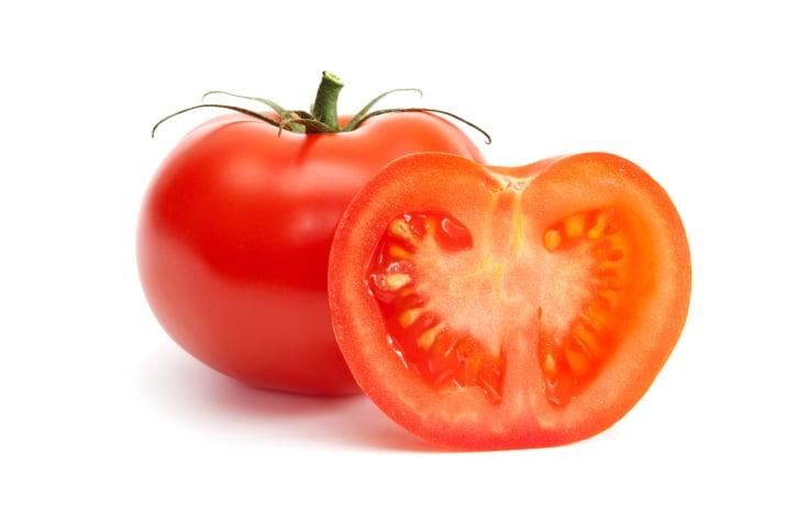 Un tomate con una mitad de tomate frente a él
