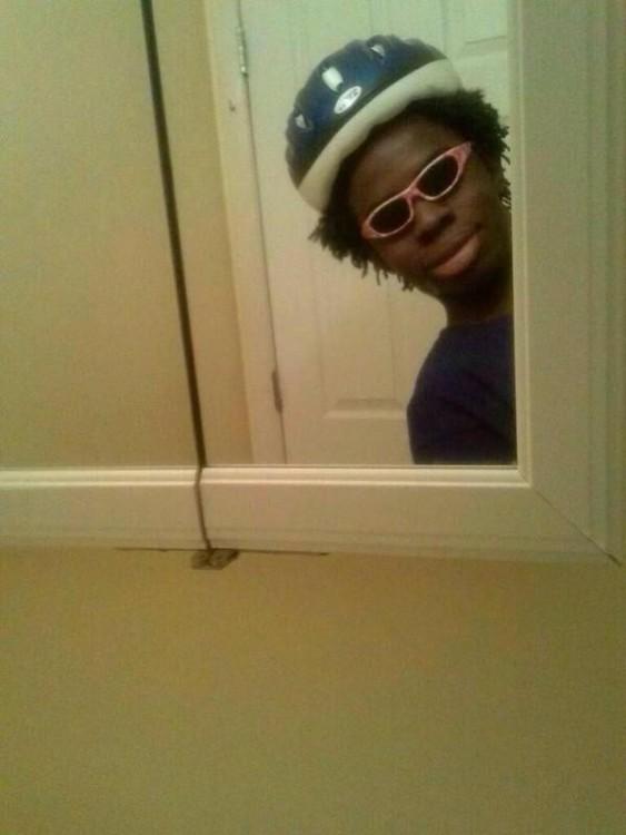Reflejo de la cara de un chico en el espejo del baño
