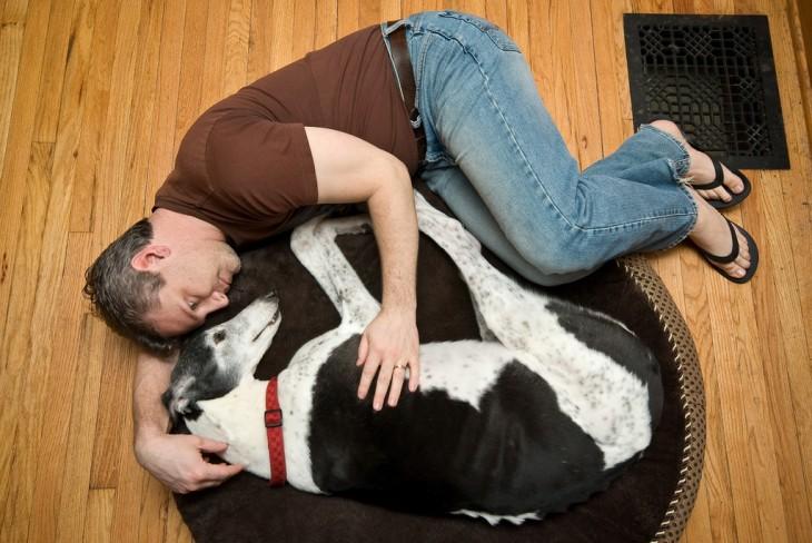 Hombre acostado abrazado de su perro en el suelo de su casa