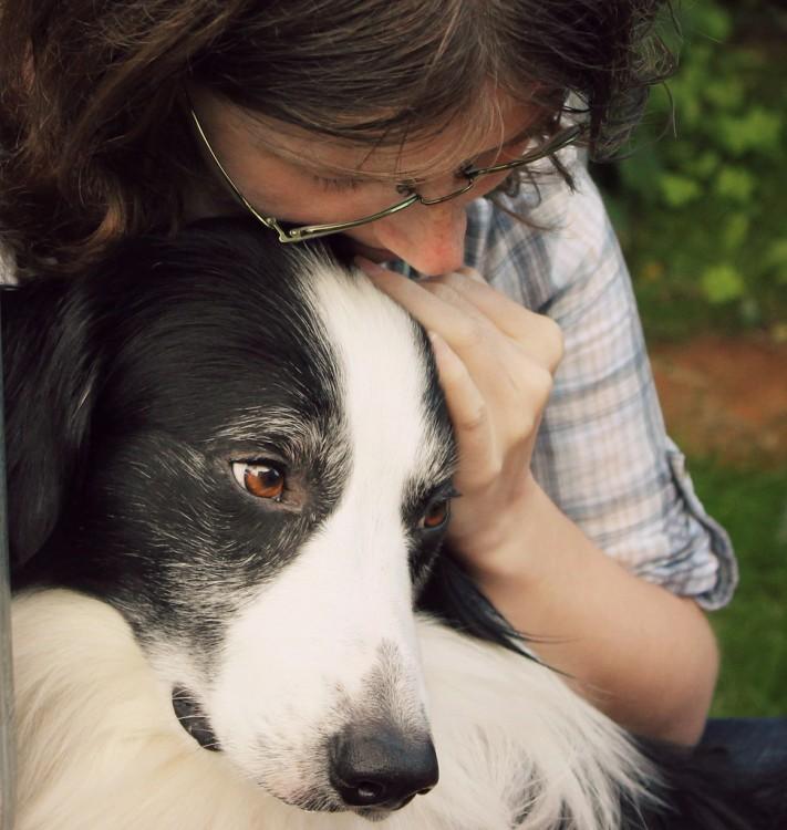 Chica abrazando a su perro con cara de tristeza