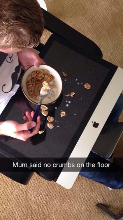 Chico comiendo cereal sobre su mac book