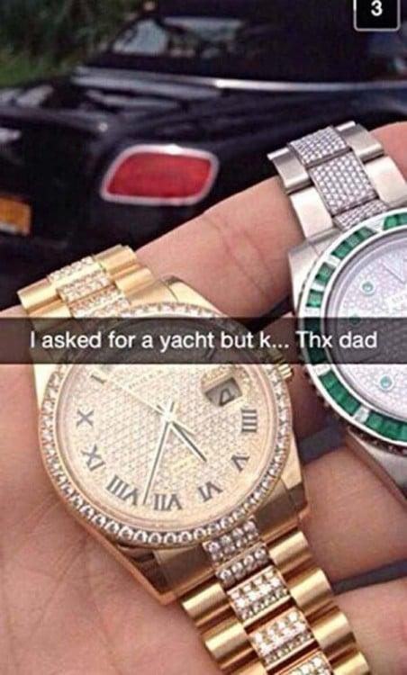 Mano de un chico sosteniendo dos costosos relojes