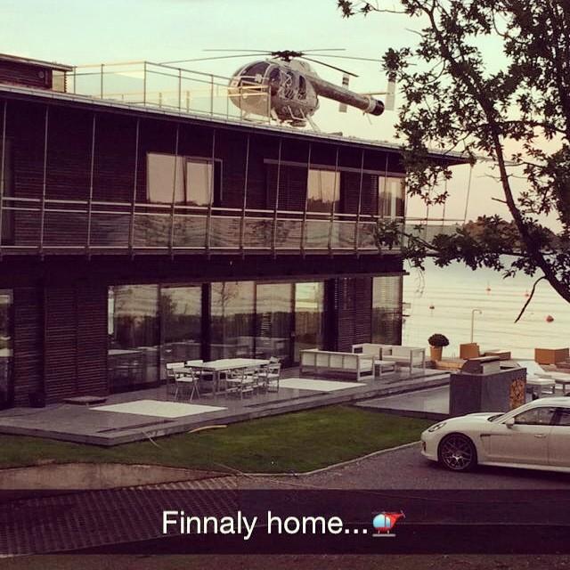 Casa con un coche estacionado y un helicóptero sobre ella