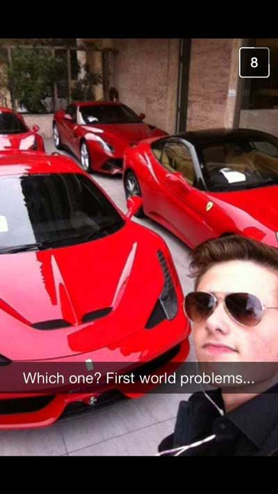 Chico tomándose una selfie con cuatro caros de lujo detrás