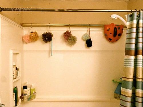 coloca una barra extra de cortina de ducha para almacenar cosas