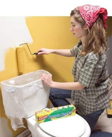 mujer arrodillada pintando una pared de color amarillo