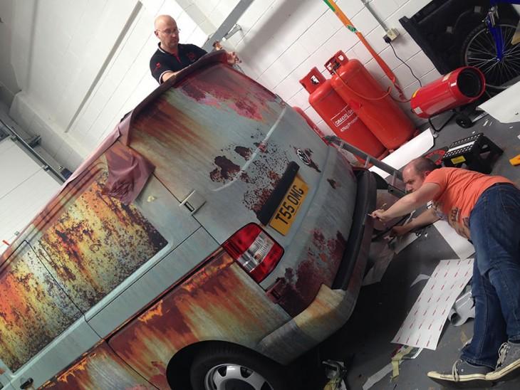 dos personas haciendo arreglos y decoración a un automóvil