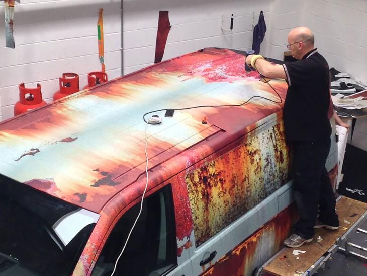 hombres en un taller colocando vinilo de oxido a una camioneta