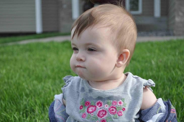 bebé mordiendose la boca en un jardin