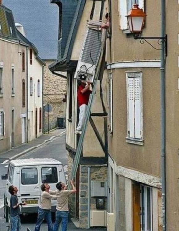 hombres tratan de subir refrigerador por la ventana de un departamento