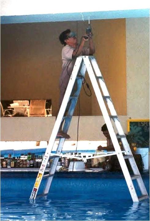 hombre arreglando la lampara de la alberca con la alberca llena