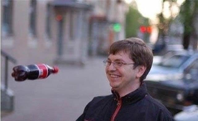 una botella de coca cola le va a pegar a un hombre en la cara
