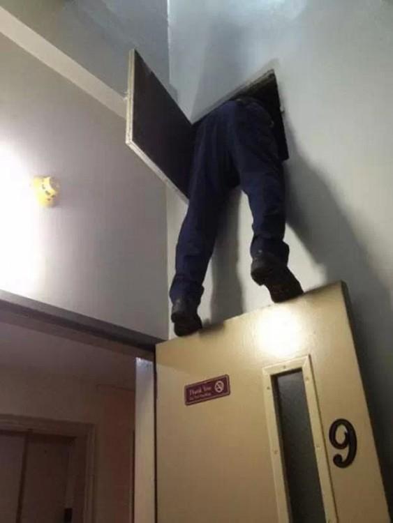 hombre parado sobre una puerta para poder checar el aire acondicionado