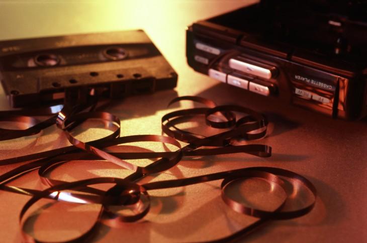 casette con la cinta de fuera a un lado de un grabadora de los años 90