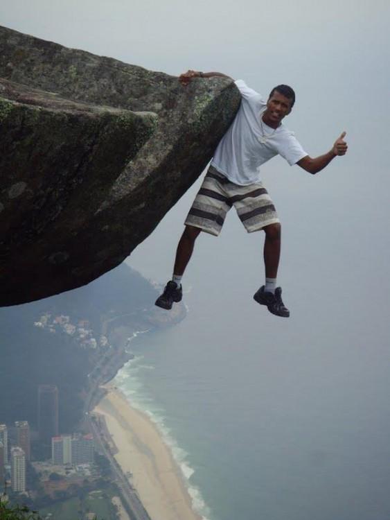 hombre tomado de una mano desde una cima alta para tomarse una fotografía