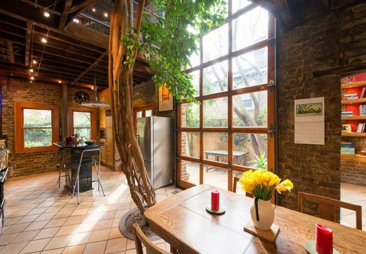 casa con un arbol dentro y un jardin muy romantico
