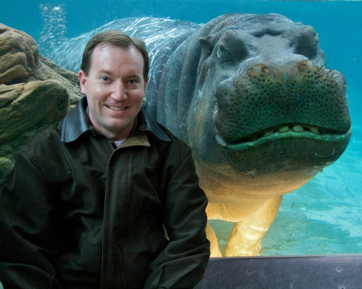 hombre tomandose una foto con un hipopotamo