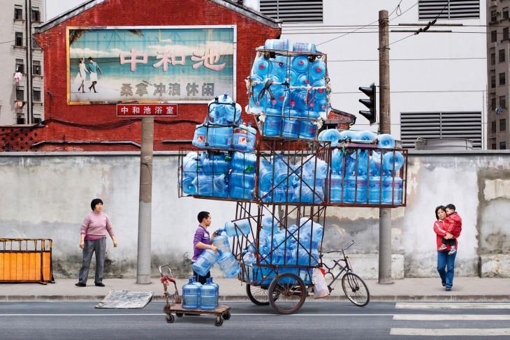 hombre con muchos garrafones en un triciclo los pasea para llevarlos hacia algun sitio donde se los cambien por dinero