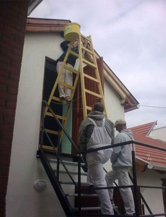hombres pintando una fachada de una forma un poco convencional de modo que su vida corre peligro mientras pintan la entrada de la casa