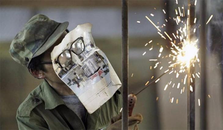 hombre con una mescara de papel hechiza mientras solda edirecto sobre su rostro